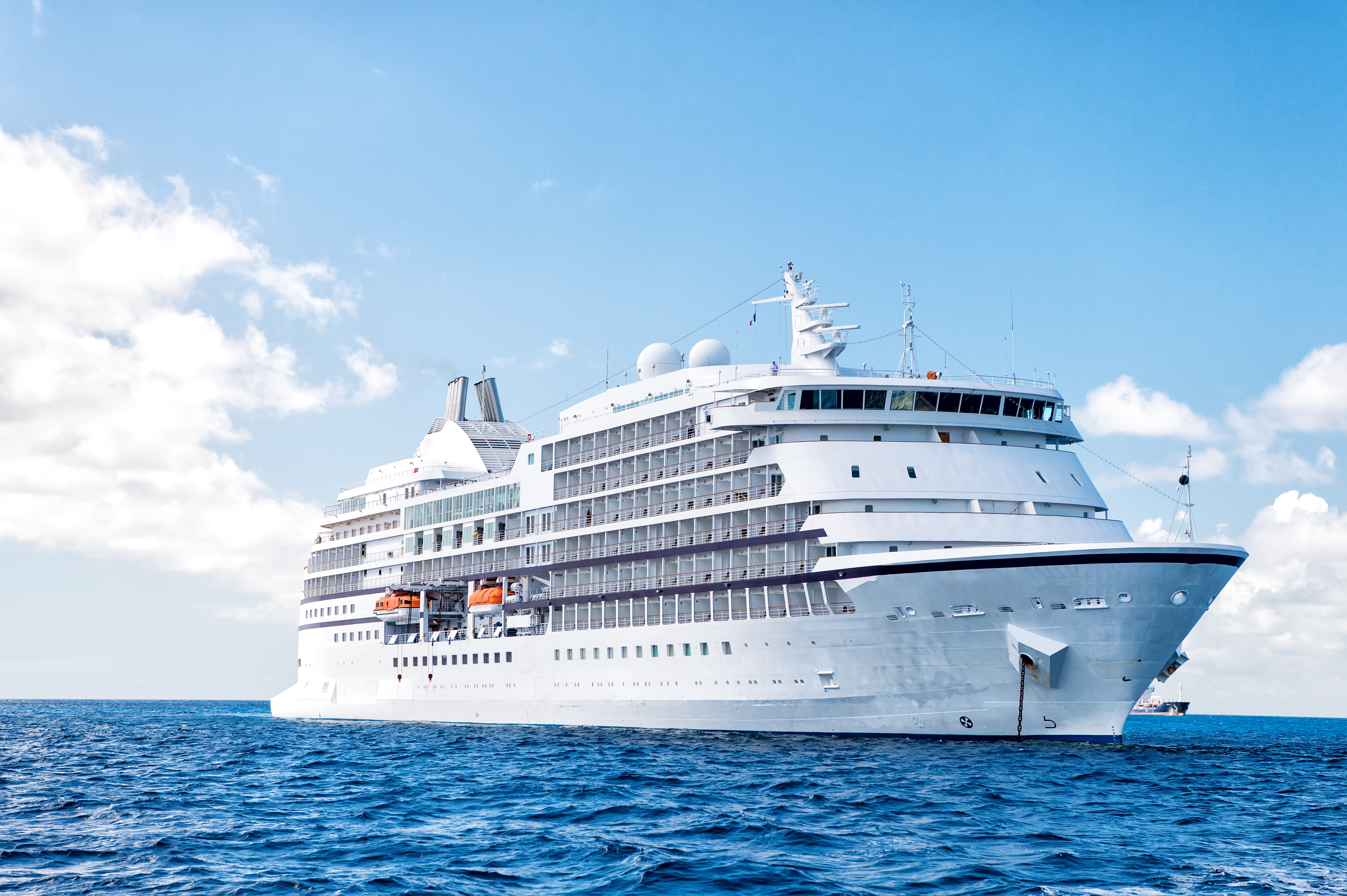 Large luxury cruise ship on sea water and cloudy sky background at sunny day at ocean